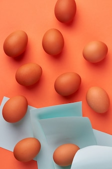 냅킨과 갈색 닭고기 달걀의 세로 샷입니다. 오렌지 배경에 고립.