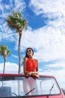 ブルネットの女性の垂直方向のショットは、晴れた日にビーチに旅行し、青い空とヤシの木を背景にsuvの車に立っています。