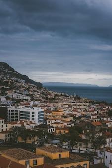 ポルトガル、マデイラ諸島、フンシャルの曇り空の下の山の建物の垂直ショット。