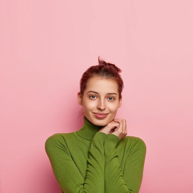 魅力的なヨーロッパの女性の垂直ショットは、顔の近くに手を保ち、カジュアルな緑のタートルネックを身に着け、カメラを直接見て、ピンクの背景の上に隔離され、あなたのための空きスペース