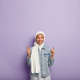 Вертикальный снимок жизнерадостной вдохновленной женщины, показывающей указательные пальцы вверх, с приятной улыбкой, с пустым пространством, в белой вуали по традиции, изолированной над фиолетовой стеной со свободным пространством.