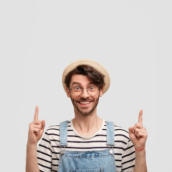 カジュアルなストライプのセーターとデニムのダンガリーを着て、上向きに、幸せな表情で陽気な男性農家の垂直ショット