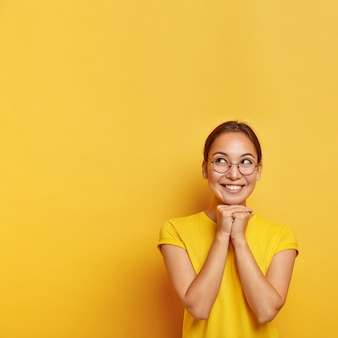 쾌활한 사려 깊은 아시아 여성의 세로 샷은 턱 아래에서 손을 함께 누르고, 멋진 것을 희망하고, 안경과 티셔츠를 입고, 노란색 벽에 고립 된 자연의 아름다움을 가지고 있습니다.