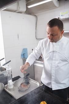 Вертикальный снимок шеф-повара, готовящего стейк из говядины на гриле в ресторане