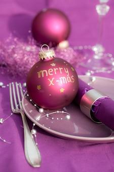 Вертикальный снимок новогоднего украшения на тарелке на праздничном столе