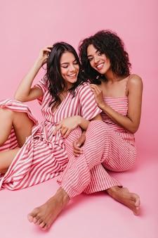美しいカールのある浅黒い肌のモデルの垂直ショット。淡いピンク色のサンドレスは、完璧な日焼けした女の子を好意的に強調します。