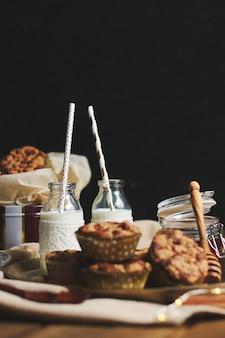 나무 테이블에 꿀, 우유와 함께 접시에 맛있는 크리스마스 쿠키 머핀의 세로 샷