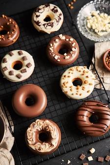 Вертикальный снимок восхитительных пончиков, покрытых бело-коричневой шоколадной глазурью на черном столе