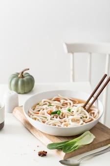 Вертикальный снимок вкусного супа с лапшой в минималистичном домашнем интерьере