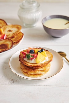 朝食時に果物を上に載せたおいしいパンケーキの縦のショット