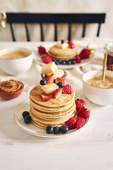 시럽과 커피 근처에 다채로운 과일과 함께 맛있는 채식 두부 팬케이크의 세로 샷