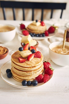다채로운 과일, 시럽 및 커피와 함께 맛있는 채식 두부 팬케이크의 세로 샷