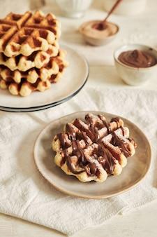 흰색 테이블에 초콜릿 딥과 함께 맛있는 와플의 세로 샷