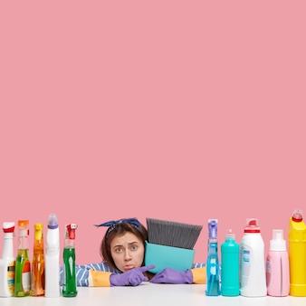 Вертикальный снимок недовольной мрачной уборщицы с расстроенным выражением лица указывает на моющие средства, несет веник