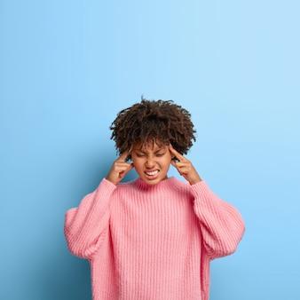 Вертикальный снимок недовольной женщины с афро, позирующей в розовом свитере