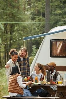 トレーラーバンでキャンプ場で屋外でピクニックを楽しんでいる友人の多様なグループの垂直ショット