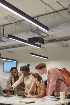 学校のitラボのテーブルに立って、コピースペースで一緒に作業し、デジタルタブレットを使用している学生の多様なグループの垂直ショット