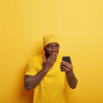 Вертикальный снимок смущенного красивого парня в очках, позирующего со своим телефоном