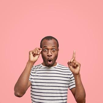 感情的な愚かなアフリカ系アメリカ人の男の垂直ショットは、上の人差し指で示しています