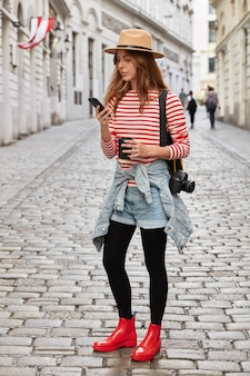 ファッショナブルな女性の垂直ショットは、帽子、ストライプのジャンパー、ショートジーンズ、ゴム製の赤いブーツを着用し、セルラーを保持します