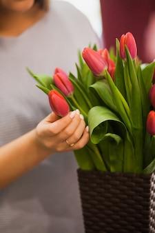 春の新鮮なチューリップのバスケットを保持している女性の手の垂直ショット。休日の準備でフラワーマーケットで女性の花屋。花のデザインコンセプト
