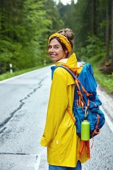 Вертикальный снимок туристки, которая гуляет в зеленом лесу