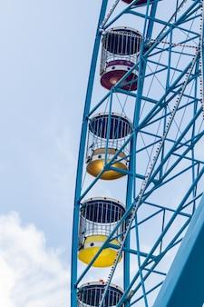 Вертикальный снимок колеса парома с пасмурным небом на заднем плане