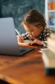 Вертикальный снимок сфокусированной девочки начальной школы, делающей домашнее задание, написание заметок в бумажной записной книжке, сидя за столом с ноутбуком. очаровательные серьезные ученицы школьницы электронного обучения онлайн с помощью компьютерного приложения.