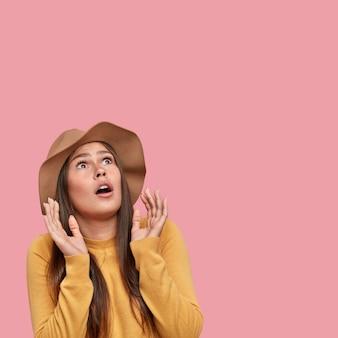 Вертикальный снимок испуганной кавказской женщины с испуганным выражением лица смотрит вверх, держит руки возле лица, пытается от чего-то защититься