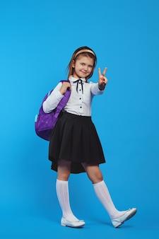 Вертикальный снимок девушки в полный рост с рюкзаком и жестом мира