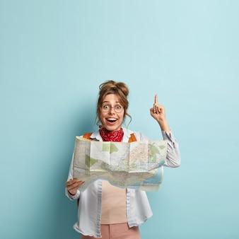 Вертикальный снимок довольной европейской женщины-путешественницы, показывающей указательным пальцем, наслаждающейся приятной поездкой