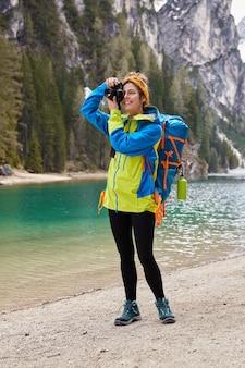 기쁜 여자의 세로 샷은 자연 풍경의 전문적인 사진을 만들고 재킷을 입습니다.