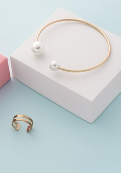 白と青の背景に真珠のブレスレットとダブルリングとゴールデンの垂直ショット