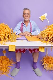 사무실 테이블에서 일하는 회색 머리 유럽 남성의 수직 사진은 공식적인 옷을 입고 그의 작업 일정은 성공적인 비즈니스 사람이 국내 분위기를 즐기는 테이블에 엉망입니다