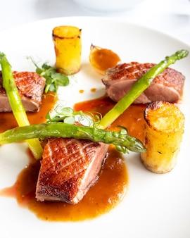 Вертикальный снимок жареного мяса с соусом и спаржей на тарелке