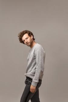 彼の頭の上にコピースペースの壁でポーズをとって、トレンディなカールした髪型と黒のジーンズと灰色のジャンパーを身に着けている無精ひげを持つハンサムなスタイリッシュなヨーロッパの男性モデルの垂直ショット。カジュアルなメンズスタイル