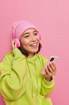 Вертикальный снимок счастливой азиатской девочки-подростка с мобильным телефоном в руке, она наслаждается прослушиванием музыки из плейлиста, имеет приятные улыбки на лице, одетая в небрежно