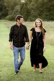 芝生のフィールドで歩きながら手を繋いでいる幸せなカップルの垂直ショット