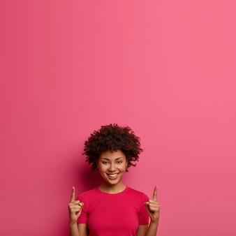 행복 곱슬 머리 젊은 여자의 세로 샷 위에 표시, 머리 위에 빈 공간을 보여주고, 즐겁게 미소 짓고, 하얀 치아를 보여주고, 분홍색 벽에 고립 된 위쪽으로 뭔가를 보여줍니다.