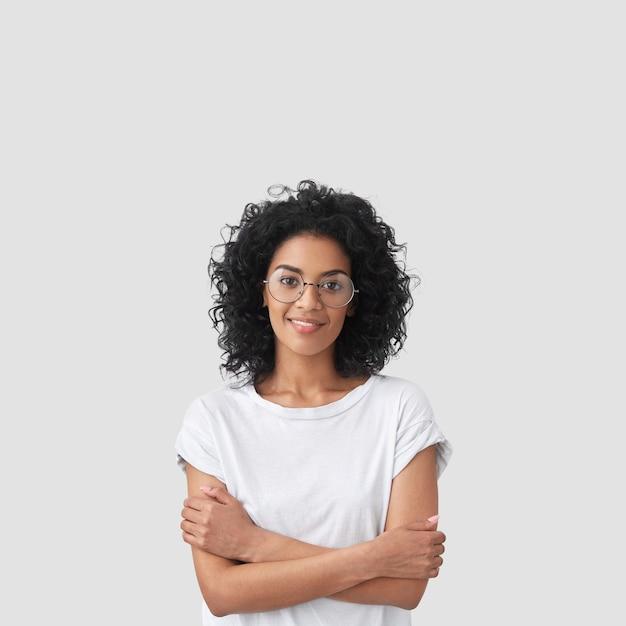 巻き毛の幸せな暗い肌の女性の垂直ショット