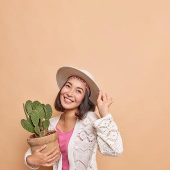 검은 머리를 가진 행복한 꿈꾸는 아시아 여성의 수직 사진은 그녀의 집 정원을 위해 냄비에 선인장을 사는 밝은 표정이 베이지색 벽 공백에 대해 페도라 니트 흰색 점퍼 포즈를 취합니다