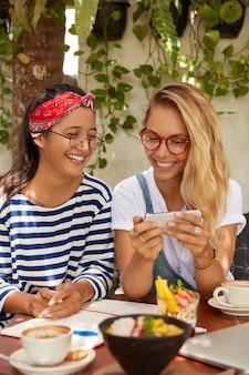 幸せな異人種間の女性の垂直ショットは良いジョークで笑い、スマートフォンで面白いビデオを見る