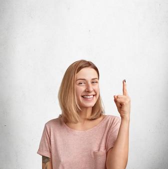 Вертикальный снимок счастливой молодой женщины с короткой стрижкой, небрежно одетой, указывает на пустое место для копирования, что-то рекламирует