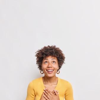 Вертикальный снимок счастливой молодой женщины с вьющимися волосами, прижимающей руки к груди, выражает благодарность, сфокусированную выше, имеет зубастую улыбку в желтом свитере, изолированном над белой стеной