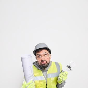 躊躇している男性の建設労働者が新しい家でリフォームを行う垂直ショットは、上に無知に集中している青写真とペイントブラシを保持します