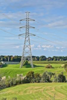 전경에 녹색 초원이 있는 고전압 전기 타워의 수직 샷