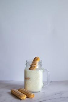 흰 벽에 쿠키가 있는 홈메이드 밀크셰이크의 세로 샷