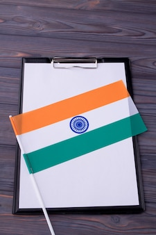 Вертикальный снимок индийского флага и буфер обмена с чистым листом бумаги