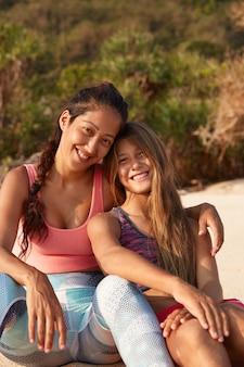 인종 간 여성의 세로 샷은 동성애 관계를 가지고 모래 해변에 앉아