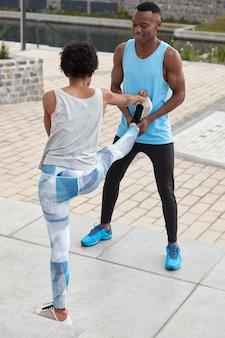남성 코치의 세로 샷은 그의 아프리카 계 미국인 여성 연수생이 스트레칭 운동을하고 야외에 서도록 도와줍니다. 스포티 한 여성이 뒤로 서서 좋은 유연성을 보여주고 다리를 높이 들고 운동화를 신습니다.